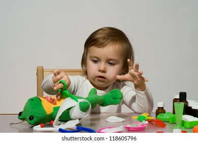 Girl playing as doctor with her toys