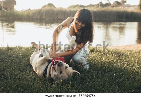 草の上で犬と遊ぶ少女