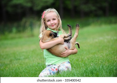 girl playing with dogs on grass