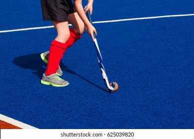 "A girl playing field hockey on blue ""wet"" turf"
