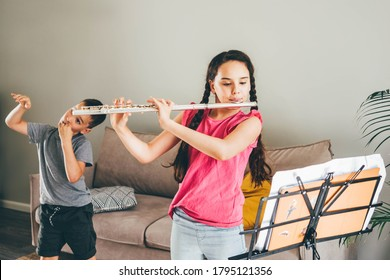 Girl playing the flute. Brother teasing his sister land having fun at home.