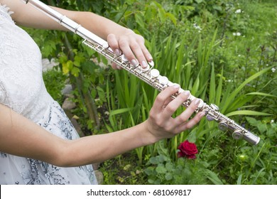 Girl playing the flute in the garden.