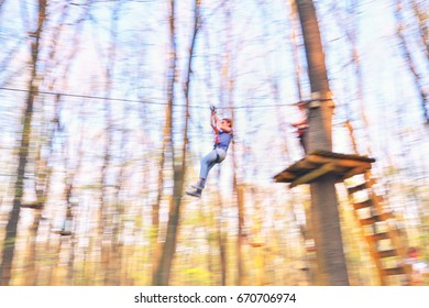 A girl is playing with flying fox tyroliana in the Eden Park from Bucharest
