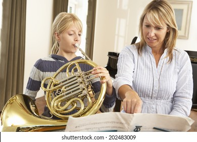 Girl playing French horn in music lesson
