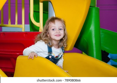 Girl playing fun in the mall, coming down from the yellow hill
