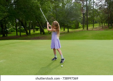 Girl playing golf, with a golf club in the air