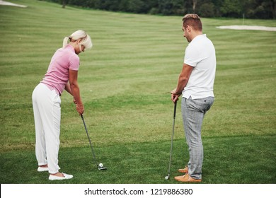 Girl playing golf and hitting by putter on green. Her teacher helps to explore the technique and make her first strikes.