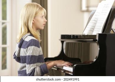 Girl playing grand piano at home