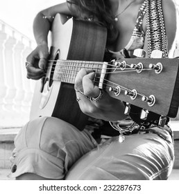 Girl playing guitar, black and white photo