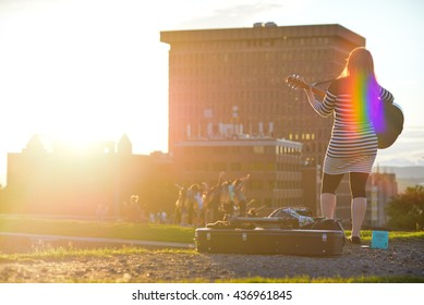 Girl playing guitar at the evening in Quebec city and with rainbow
