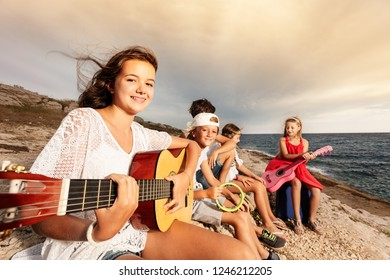 Girl playing guitar with her friends on the beach