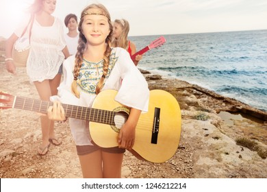 Girl playing guitar for her friends on the beach