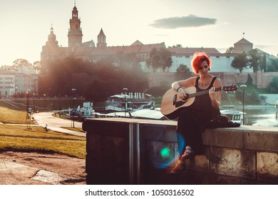 Girl playing the guitar on the background of the old city Cracow