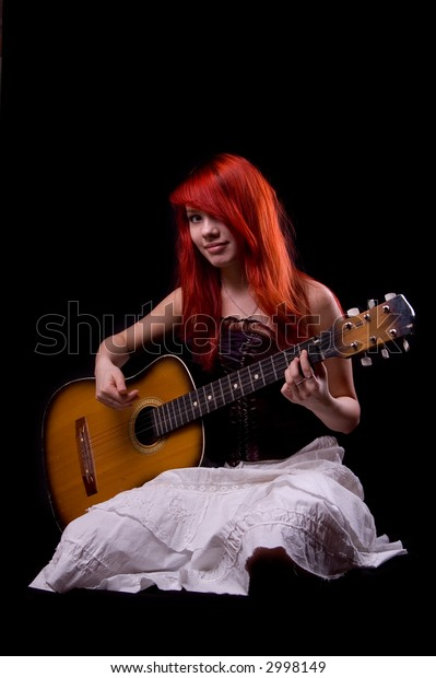 Girl playing a guitar on black background