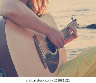 Girl playing guitar at the seacoast