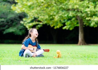 Girl playing guitar to teddy bear