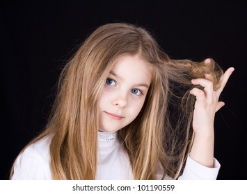girl playing with hair on a black background