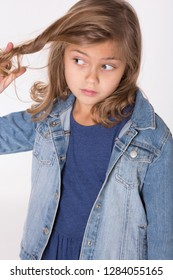 Girl playing with hair. To twist a lock of hair on a finger.