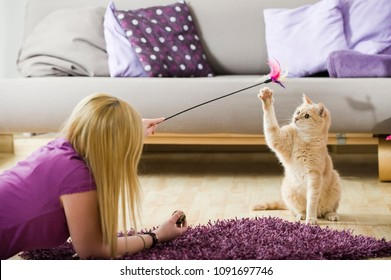 Girl playing with her cat