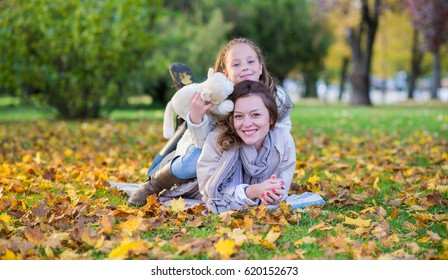 Girl playing with her mother in autumn park