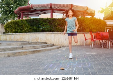 Girl playing hopscotch game on the asphalt on playground.