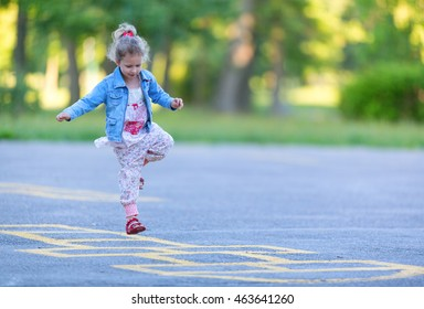Girl is playing hopscotch game on the asphalt