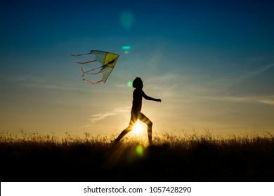 A girl playing kite during sunset