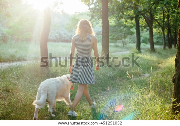 girl playing with labrador retriever dog in park