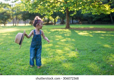 Girl playing with too large straw hat