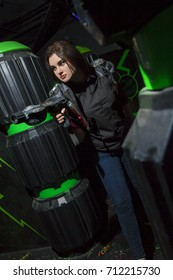 A girl are playing laser pistols in a dark room