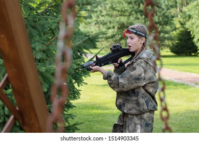 Girl playing in lasertag shooting game, girl with a gun, war simulation.