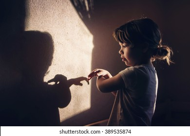 The girl is playing with light and shadow. Shadow play on the wall