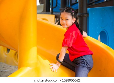 The girl is playing in the middle of the playground. With colorful plastic slide for children