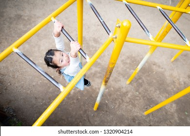 Girl playing with monkey bars