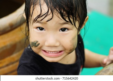 A girl playing muddy puddle. She is naughty
