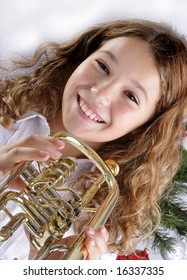 girl playing music instrument and christmas tree
