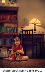 A girl is playing with an old vintage doll. Image with selective focus and toning