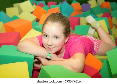 girl playing on the covered Playground on the trampoline with soft foam multi-colored cubes. the concept of childhood.