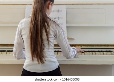 Girl playing on white piano. A view from the back of the girl sitting at the piano.