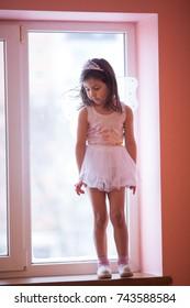 Girl playing on the windowsill