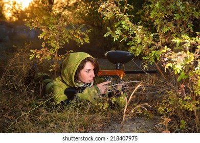 Girl playing paintball in a green protective suit.