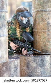 girl playing paintball in overalls with a gun