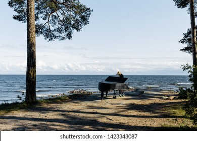 girl playing the piano by the ocean