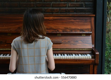 The girl was playing piano as her favorite hobby.