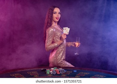 Girl playing poker at casino, holding glass of champagne, two aces. Posing at table with chips, money on it. Black, smoke background. Close-up.