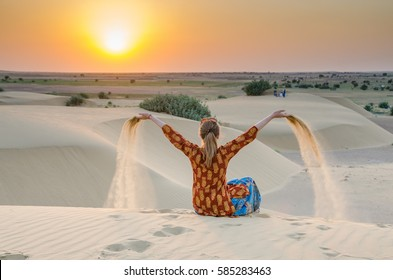 A girl playing with sand at sunset in Thar Desert, Rajasthan, India.