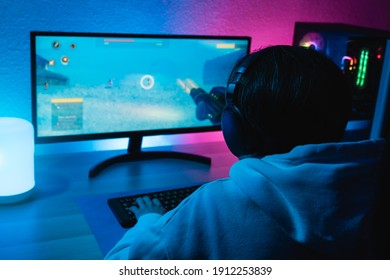 Girl playing shooter online video game - Technology trend concept - Main focus on headphones