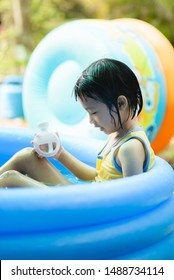 The girl is playing in the small pool temporarily. During the hot day time It's a fun outdoor activity for children. But must be careful about health.