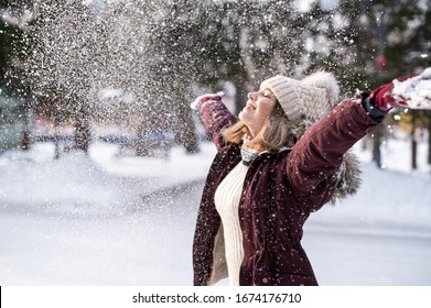 Girl playing with snow in park. Portrait of the happy girl wearing snowy winter clothes