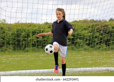 Girl playing soccer in front of the goal showing ball control